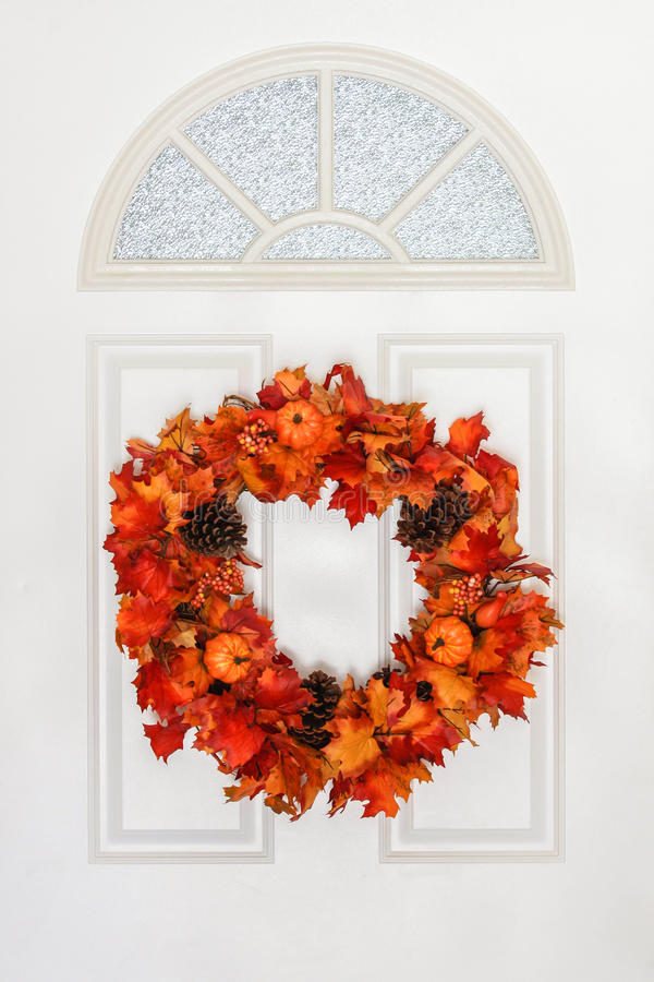 Autumn Wreath Hanging on White Door. Autumn wreath on white Colonial style door. Made up of Maple leaves of orange, yellow, red hues with pine cones and small stock image