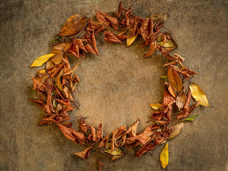 Autumn wreath. On a rustic wooden background with empty space with orange and yellow leaves stock photography