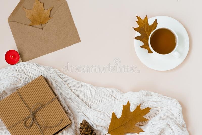 Autumnal flat lay with white knitted plaid, hot Cup of tea and fallen brown leaves, crab envelope, gift box. Top still life autumn stock image