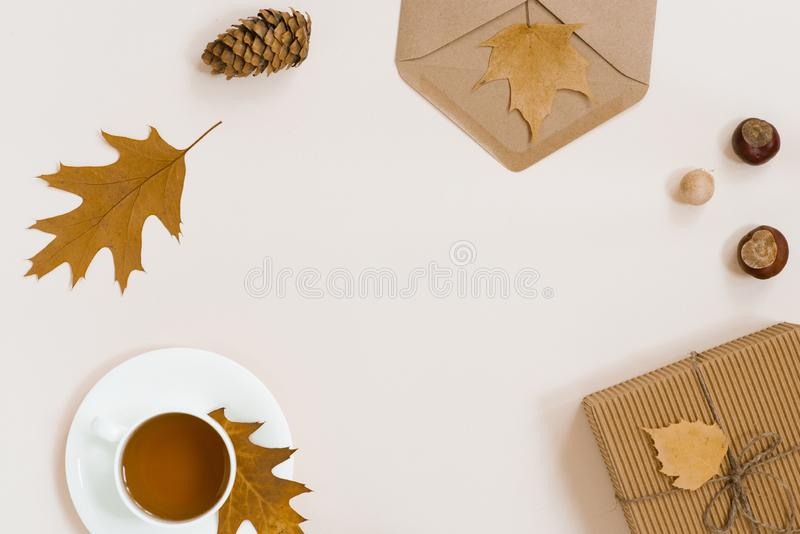 Autumnal flat lay with white knitted plaid, hot Cup of tea and fallen brown leaves, crab envelope, gift box. Top still life autumn. Concept on beige light stock photo
