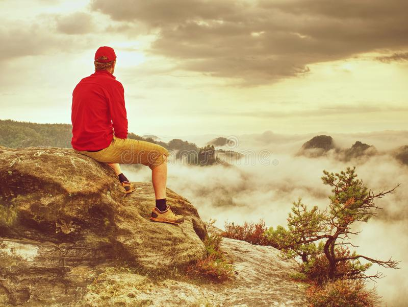Autumnal misty morning in wild nature. Hiker in sports wearing. Stand on sharp peak and watching natural show in valley bellow wonderful winter weather trousers stock photography