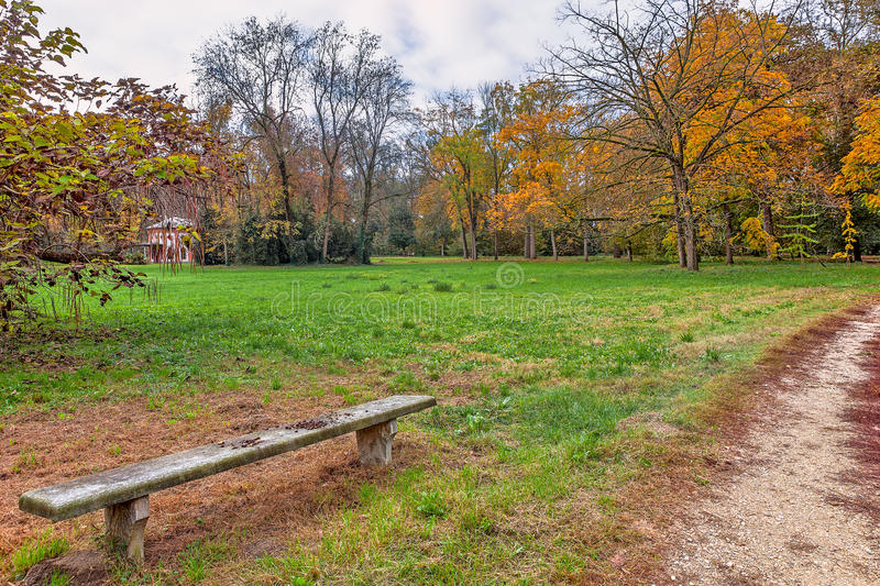 Autumnal park of racconigi, Italy. Stone bench and narrow pathway in autumnal park of Racconigi, Italy royalty free stock photography