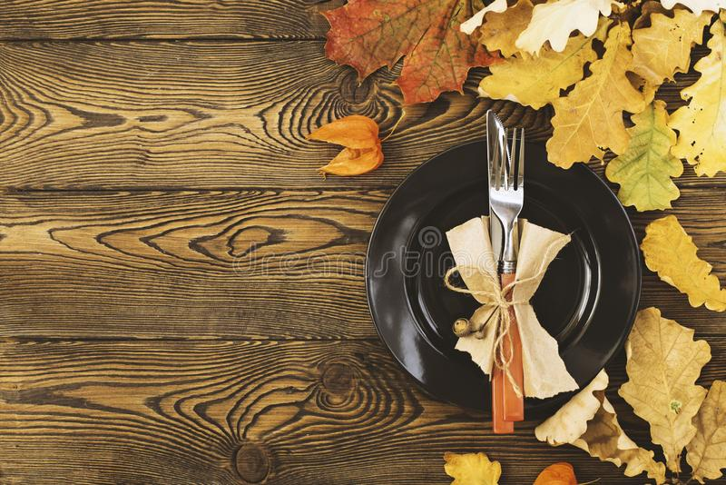 Autumnal table setting for Thanksgiving dinner. Empty plate, cutlery, colored leaves on wooden table. Fall food concept. royalty free stock photography