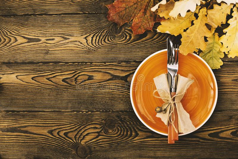 Autumnal table setting for Thanksgiving dinner. Empty plate, cutlery, colored leaves on wooden table. Fall food concept. royalty free stock photos