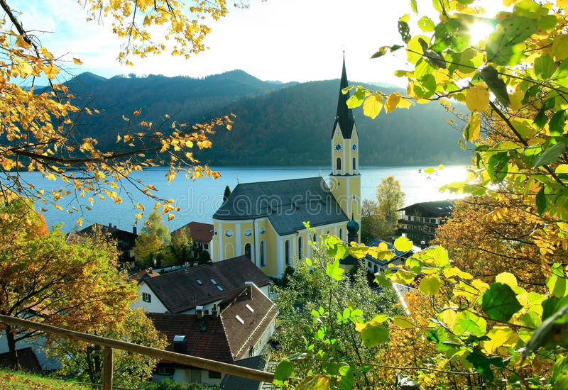 Autumnal view through branches to schliersee lake and church. Upper bavaria, germany royalty free stock photography