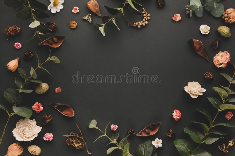 Autumnal-winter concept with dried flower, branches of eucalyptus, leaves and berries on dark background. Frame of plants. Flat stock photo