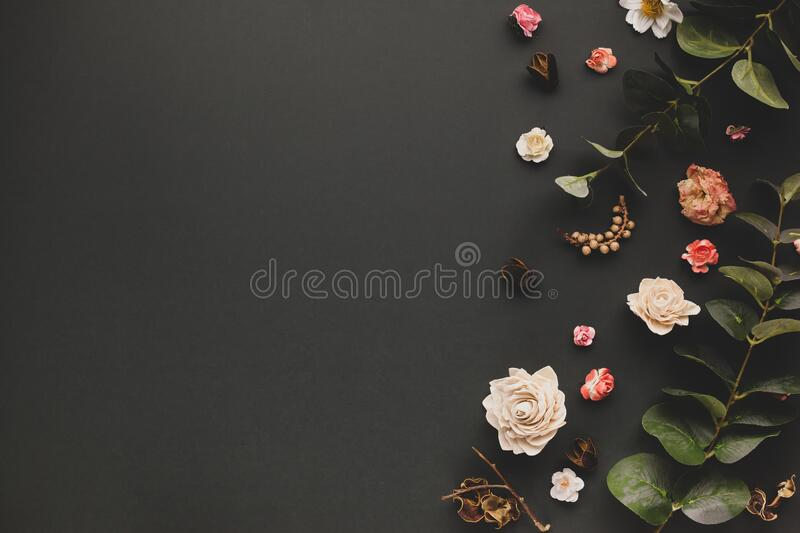 Autumnal-winter concept with dried flowers, branches of eucalyptus, leaves and berries on dark background. Frame of plants. Flat stock photography