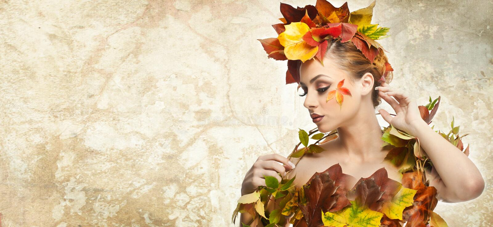 Autumnal woman. Beautiful creative makeup and hair style in fall concept studio shot. Beauty fashion model girl with fall makeup. Autumnal woman. Beautiful royalty free stock images