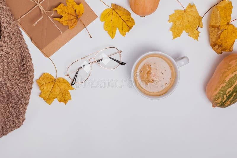 Autumncomposition créatif avec le ciffee et feuilles jaunes sur la table blanche image libre de droits