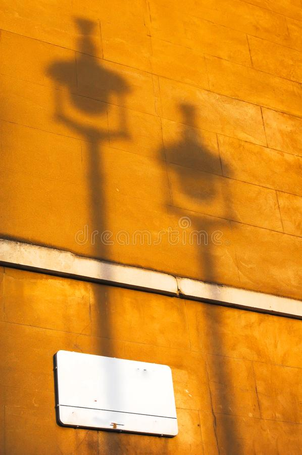 Autumnul orange sunset light casts shadow of 2 street lamps on the side of a London limestone building royalty free stock images