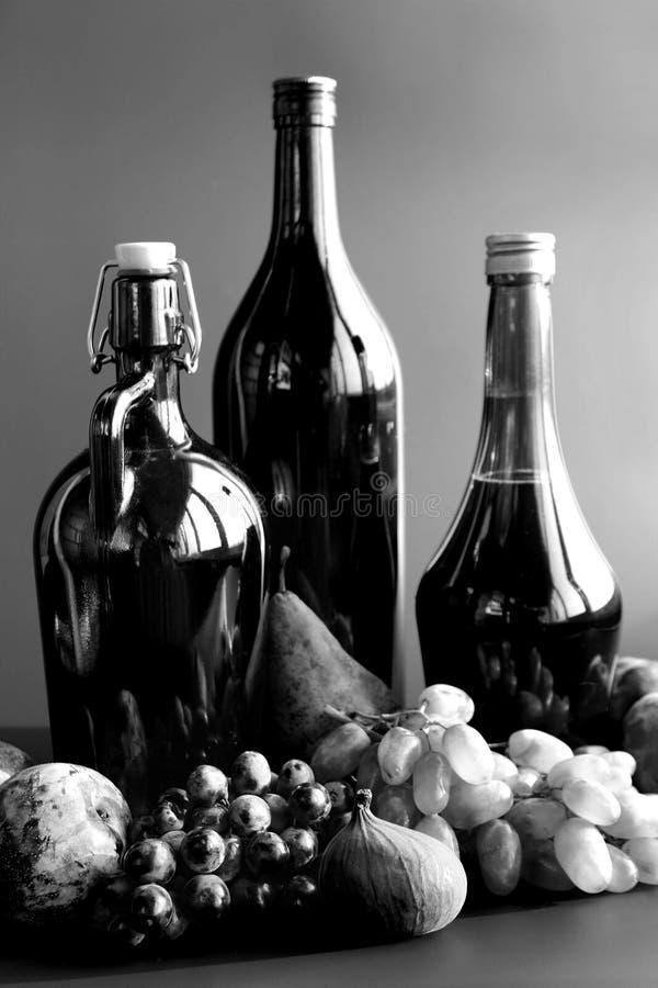 Autunno bianco e nero ancora in vita con bottiglie di vino e frutta fotografie stock libere da diritti