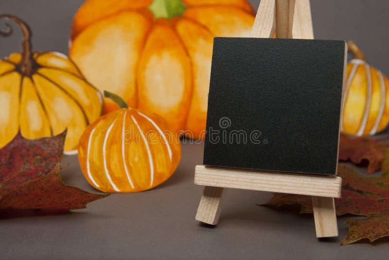 Autunno, zucche di Halloween e mini lavagna e foglie di acero della lavagna Backgroud grigio, spazio della copia fotografia stock