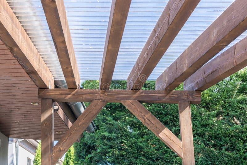 Auvent d'une terrasse faite de bois et feuilles ondulées transparentes image stock