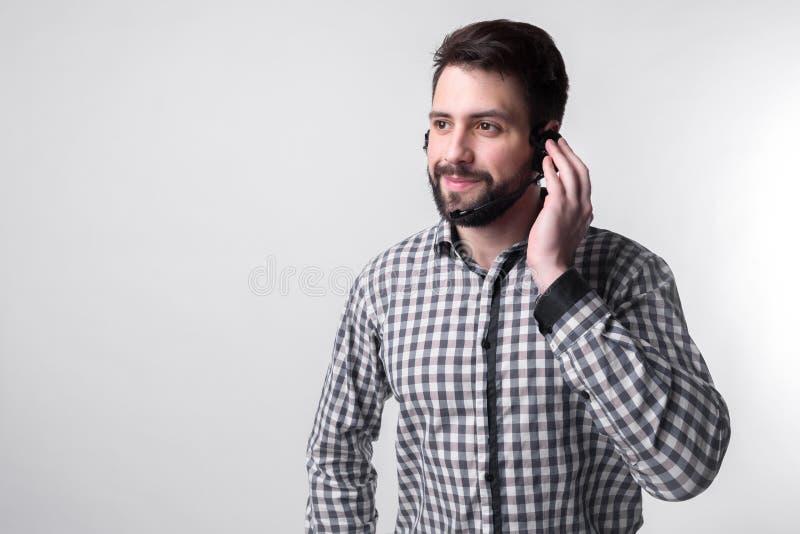 Auxílio pelo telefone O centro de atendimento do empregado ajuda seus clientes sobre o telefone Homem farpado isolado no branco imagem de stock