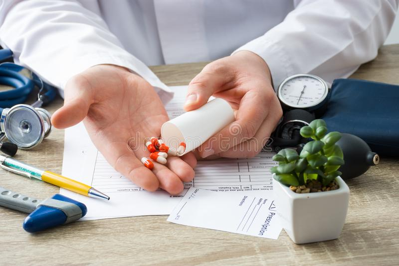 Aux médecins le médecin de rendez-vous montre les capsules patientes, qui ont vidé dans la main du conteneur avec le foyer en mai photographie stock libre de droits