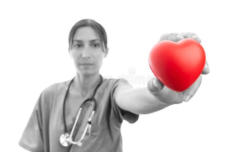 Auxiliar médico que presenta el corazón rojo foto de archivo