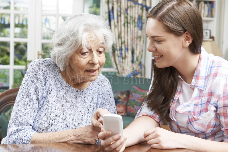 A avó adolescente da neta mostrando como usar o Phon móvel foto de stock royalty free