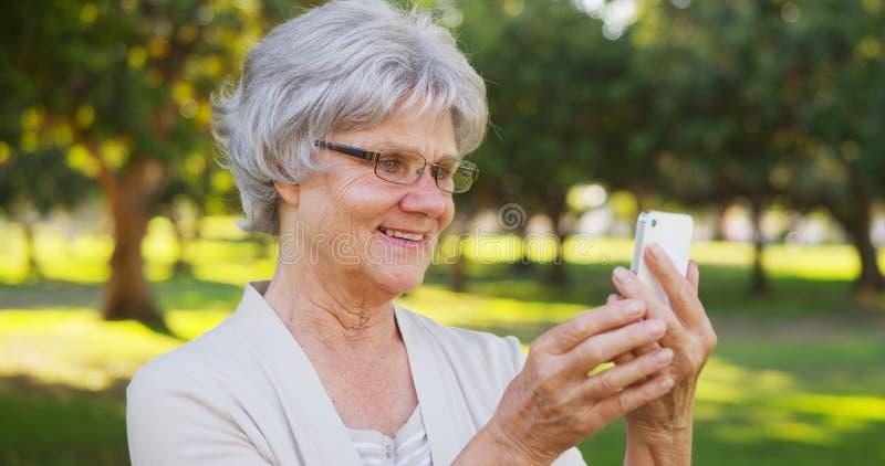 Avó anca que toma selfies no parque imagem de stock