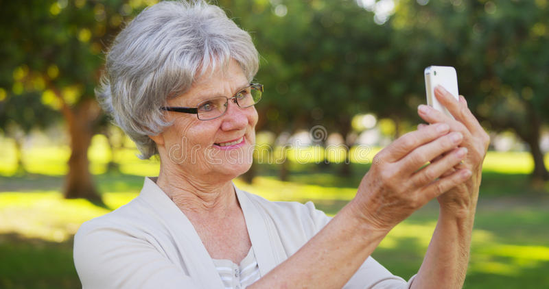 Avó anca que toma selfies no parque fotografia de stock
