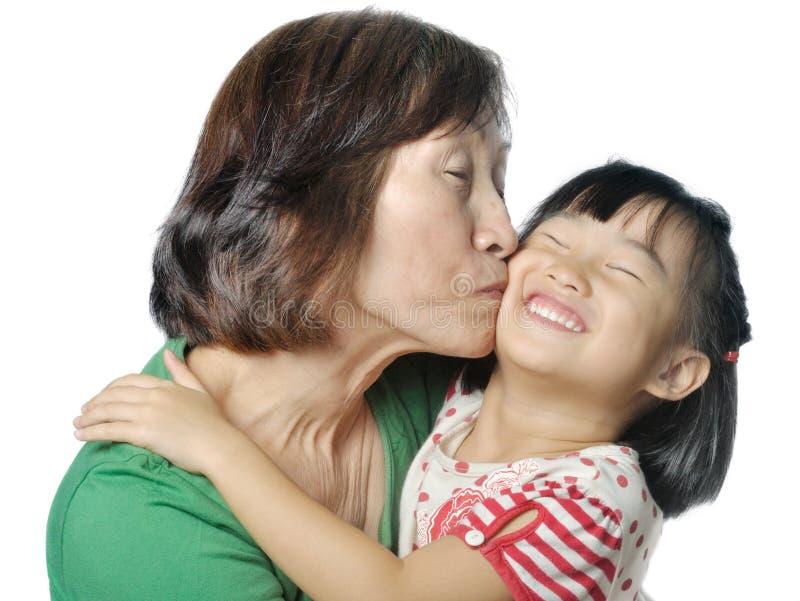 Avó asiática que beija o mordente da sua neta fotografia de stock