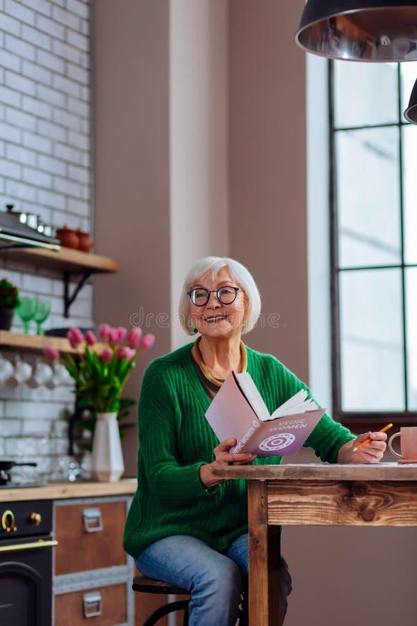Avó bonita que sorri a alguém que chama ao manter um livro imagem de stock