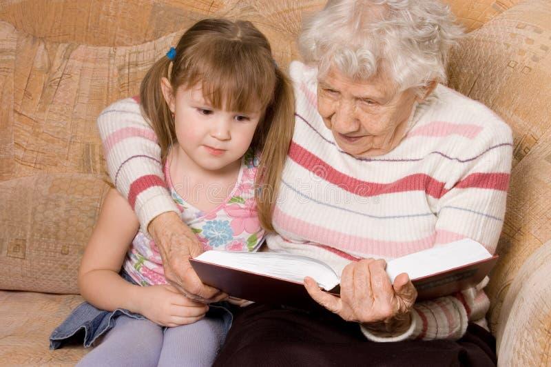 A avó com a neta leu o livro imagem de stock royalty free