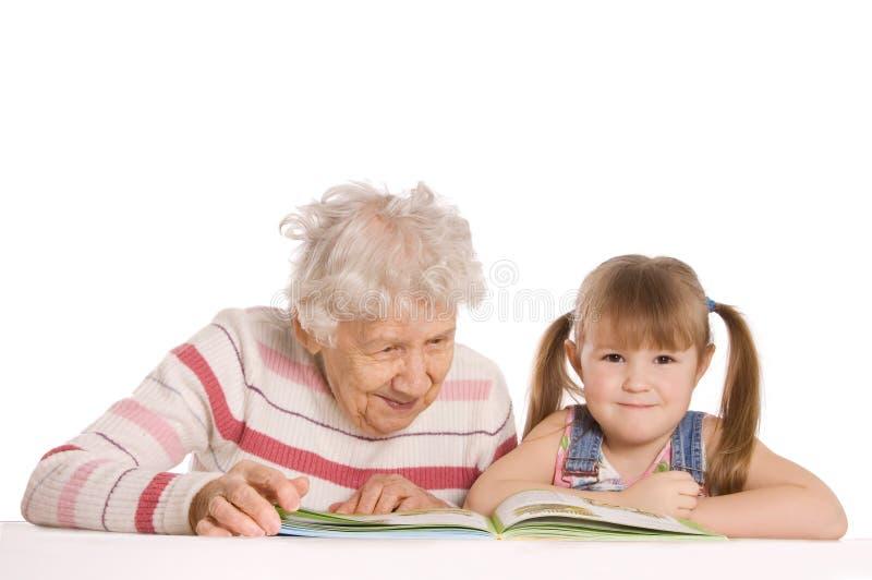 A avó com neta leu o livro foto de stock
