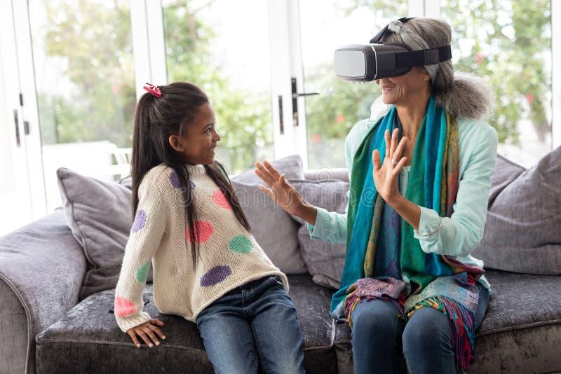 Avó com a neta que usa auriculares da realidade virtual na sala de visitas imagens de stock