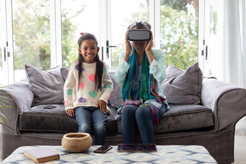 Avó com a neta que usa auriculares da realidade virtual na sala de visitas imagens de stock royalty free
