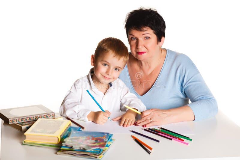 A avó com neto aprende e tira na tabela em um fundo branco fotos de stock royalty free