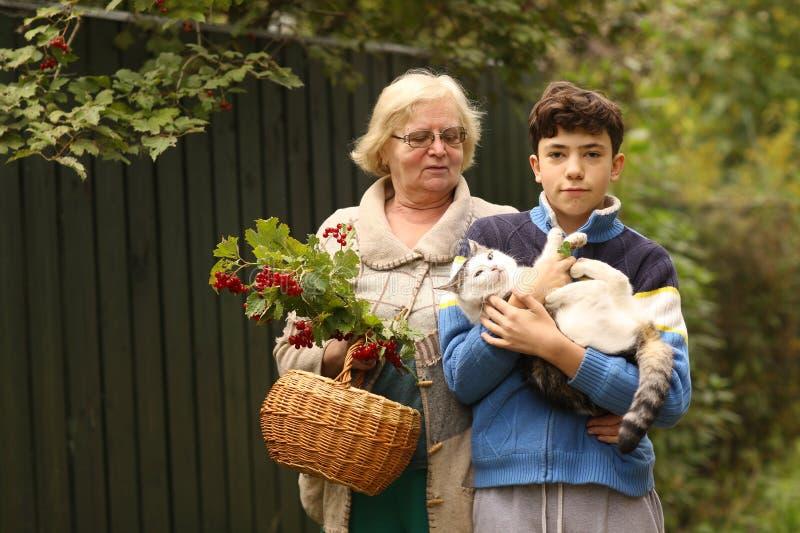 Avó com o neto com fim do viburnum e do gato acima da foto no fundo verde do jardim imagem de stock