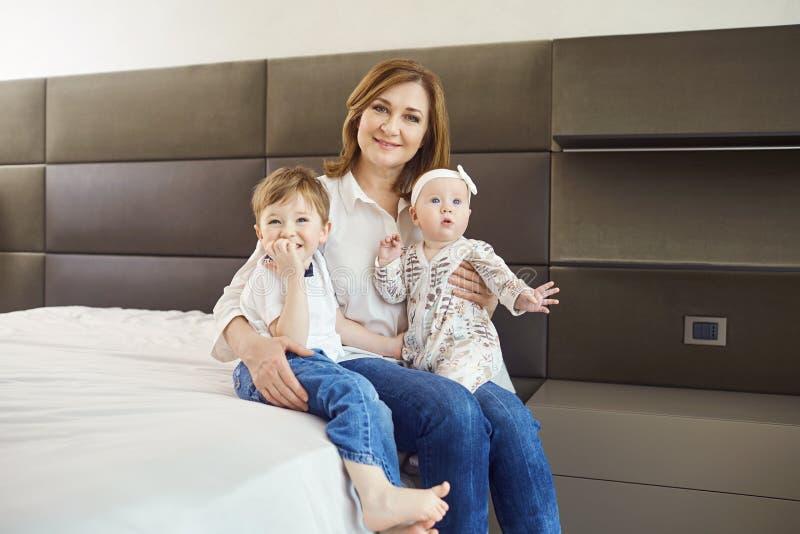 Avó com os netos na cama na sala fotografia de stock royalty free