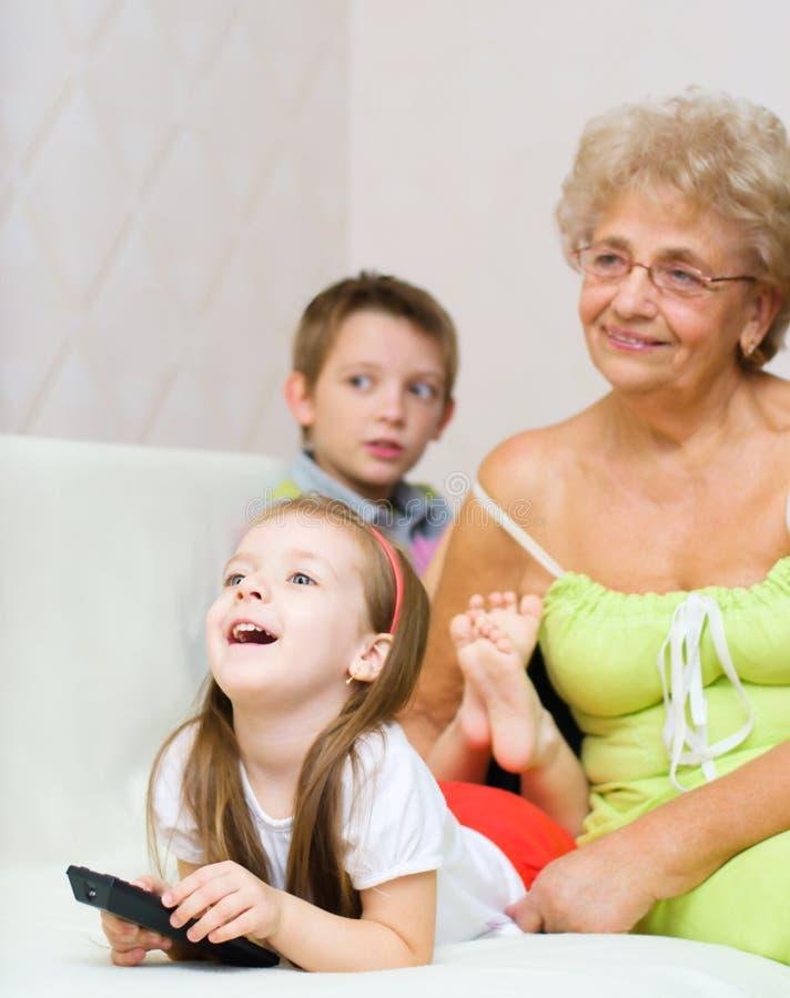 A avó com seus netos está olhando a tevê imagem de stock