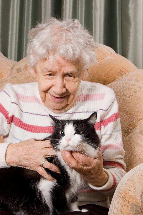 A avó com um gato em um sofá imagem de stock royalty free