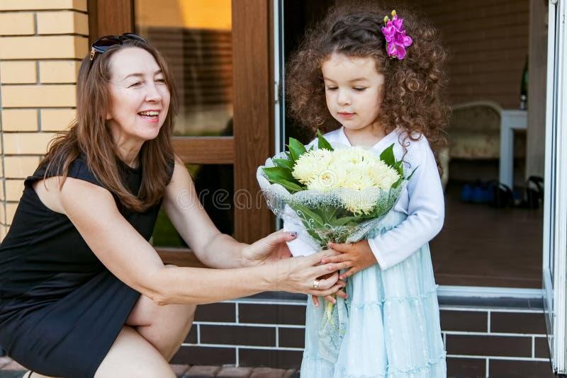 A avó dá o ramalhete da neta das flores foto de stock royalty free