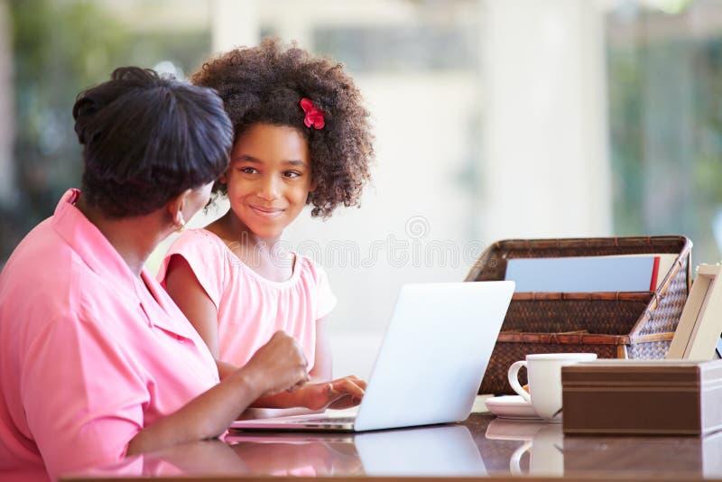 Avó de ajuda da neta com portátil foto de stock royalty free
