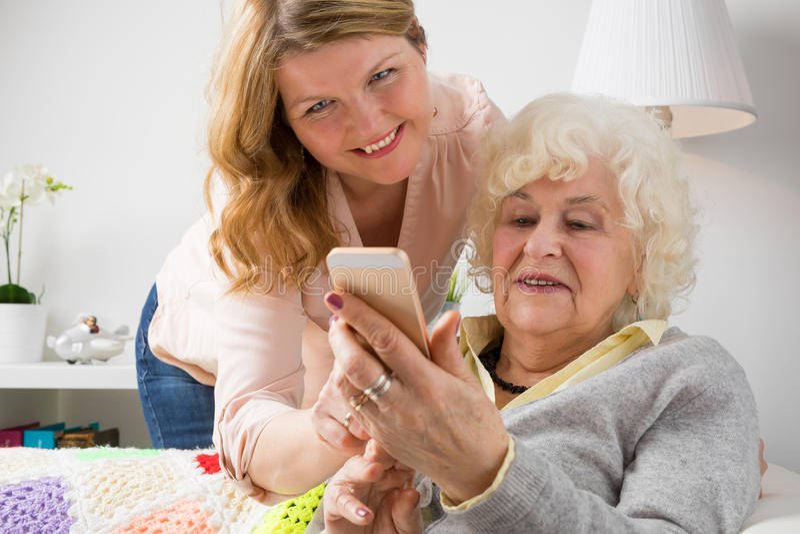 Avó de ensino da neta como usar o telefone esperto fotos de stock