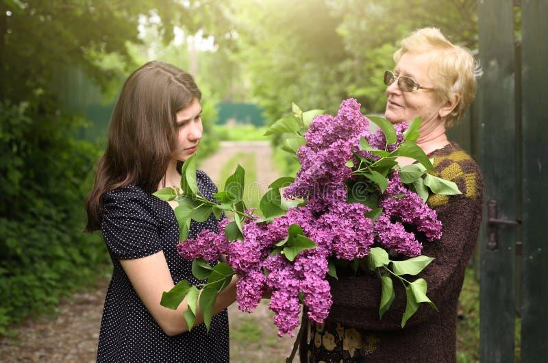 Avó e filha grande com ramalhete lilás imagens de stock