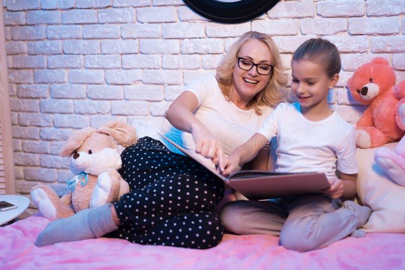 A avó e a neta estão lendo o livro do lange na noite em casa foto de stock royalty free
