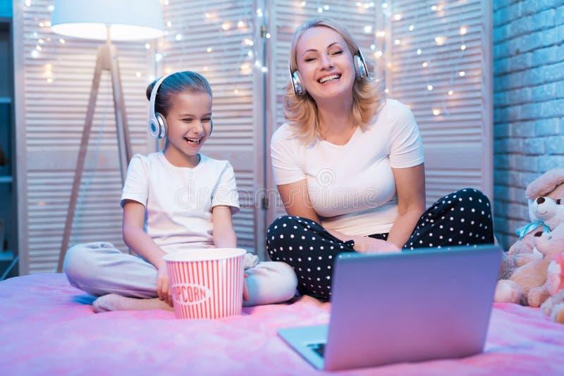 A avó e a neta estão rindo o filme de observação na noite em casa foto de stock