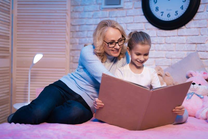 A avó e a neta são livro de leitura na noite em casa foto de stock