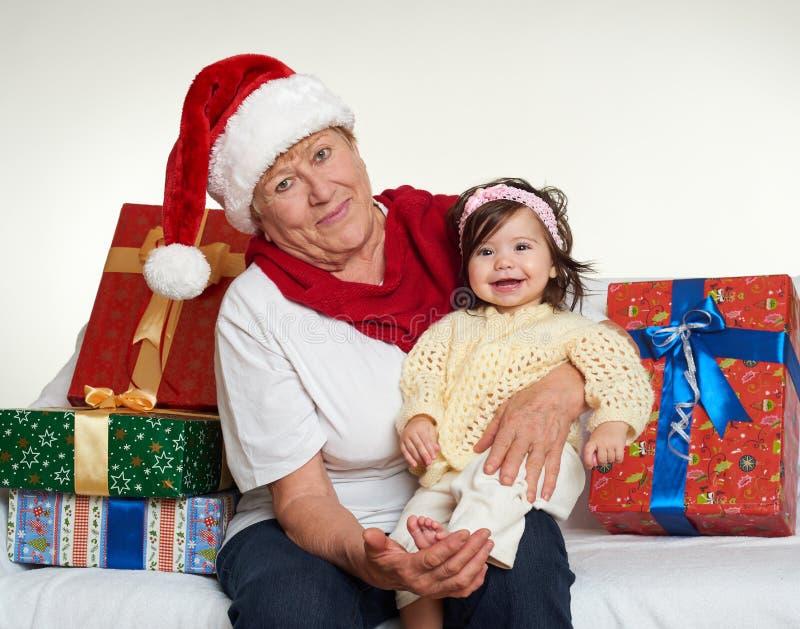 A avó e a neta vestiram-se em Santa que o chapéu com caixas de presente se senta no sofá, fundo branco Véspera de ano novo e feri fotografia de stock