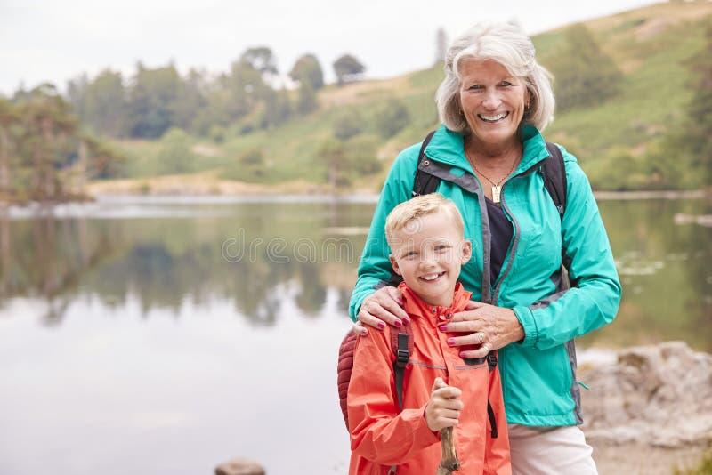 Avó e neto que estão junto perto de um lago no campo que sorri à câmera, fim acima, distrito do lago, Reino Unido fotografia de stock
