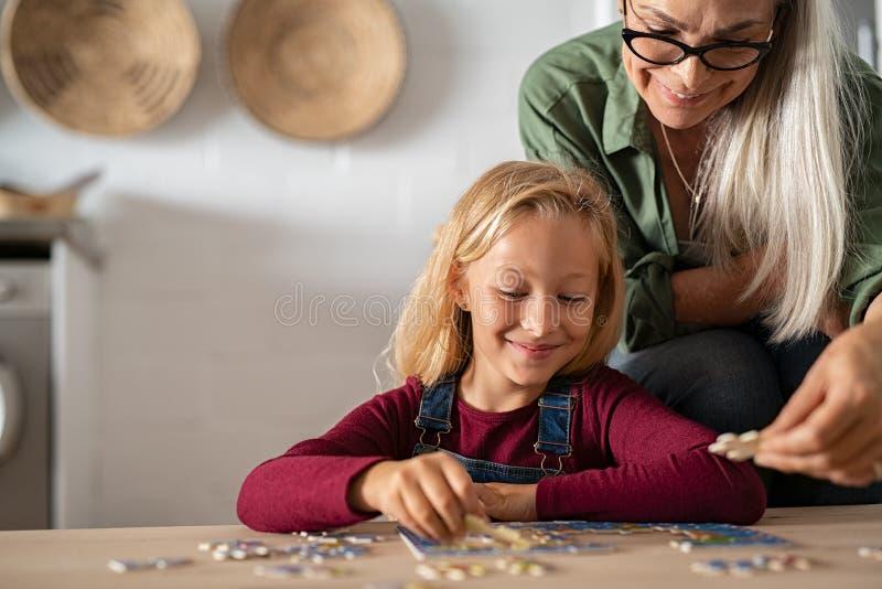 Avó e neto que resolvem o enigma de serra de vaivém imagens de stock