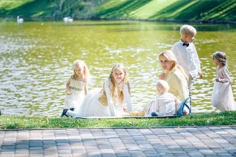Avó e netos que apreciam o piquenique em um parque Avó que joga com crianças em um fu exterior do verão ensolarado da floresta do fotografia de stock