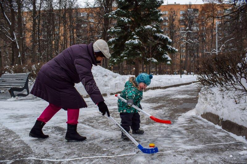 A avó e o neto com dois anos pequeno têm o divertimento que joga o hóquei no parque no inverno imagem de stock royalty free
