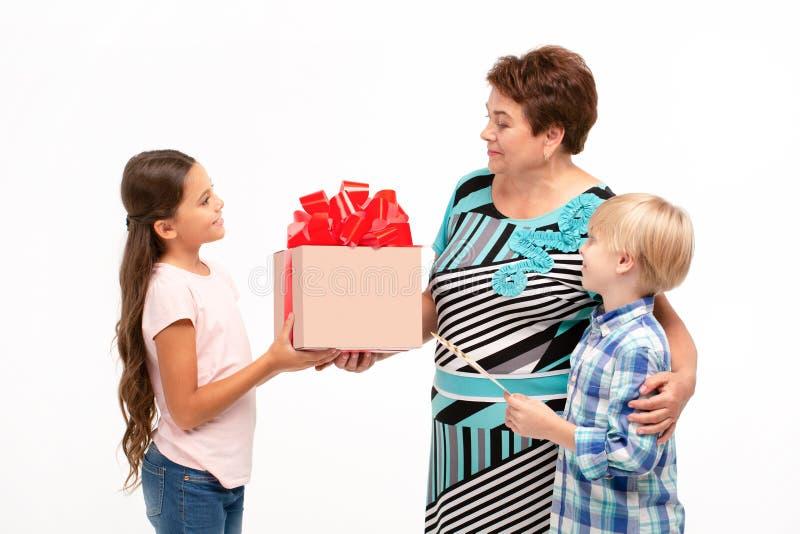 A avó e seus netos que trocam presentes fotos de stock royalty free