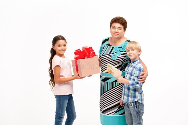 A avó e seus netos que trocam presentes fotografia de stock royalty free