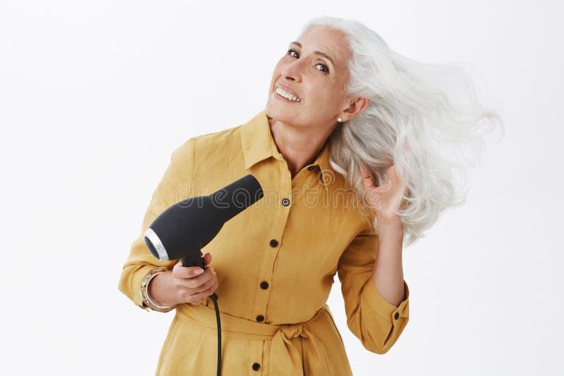 Avó elegante encantador com o cabelo cinzento que está no direito de dobra do revestimento amarelo na moda, fazendo últimas prepa fotos de stock royalty free