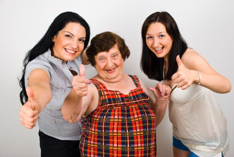 A avó feliz com netas dá os polegares fotos de stock royalty free